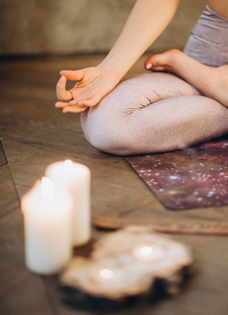 Hand in meditation pose, candles nearby